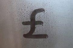 Il simbolo delle libbre inglesi è scritto con un dito sulla superficie del vetro appannato fotografia stock libera da diritti