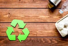 Il simbolo di riciclaggio dei rifiuti con immondizia sulla cima di legno del fondo rivaleggia Immagini Stock Libere da Diritti