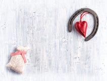 Il simbolo a ferro di cavallo di fortuna, il cuore rosso ed il regalo insaccano Immagine Stock