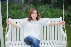 Il singolo adulto asiatico delle donne si rilassa la seduta al banco dell'oscillazione nel parco fotografia stock libera da diritti