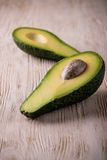Il singolo avocado ha diviso a metà sul bordo di legno bianco Fotografie Stock Libere da Diritti