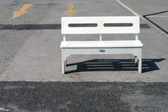 Il singolo banco di legno bianco è disposto nella luce solare di pomeriggio sul pavimento di calcestruzzo del parcheggio vuoto, l Immagini Stock Libere da Diritti
