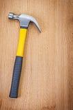 Il singolo martello da carpentiere con giallo ed il nero rubbered la maniglia su legno Fotografia Stock Libera da Diritti