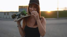 Il skateboarder della donna porta il suo pattino su una spalla stock footage