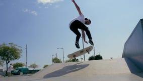 Il skateboarder fa un trucco all'aperto video d archivio