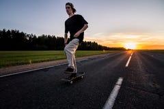 Il skateboarder guida sulla strada vuota al bello tramonto fotografia stock libera da diritti