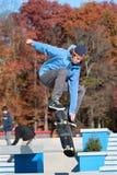 Il skateboarder va disperso nell'aria eseguendo il trucco Immagini Stock Libere da Diritti