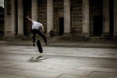 Il skateboarder vola attraverso l'aria nell'mezzo acrobazia fotografie stock