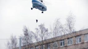 Il soccorritore scende dall'elicottero sul tetto di costruzione per l'operazione di salvataggio stock footage