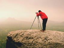 Il soggiorno dell'artista con il treppiede sulla sommità e prende le immagini del coutryside autunnale Paesaggio nebbioso Fotografie Stock