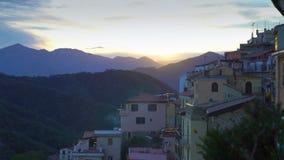 Il sol levante illumina i tetti di una città medievale nelle montagne archivi video