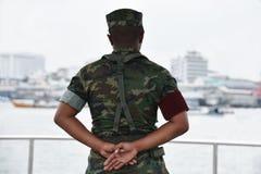 Il soldato in cammuffamento uniforma, mani dietro le sue parti posteriori immagine stock libera da diritti