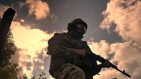 Il soldato caucasico resistente che tiene il gin automatico sta stando fermo, vista stupefacente dei cieli con il sole i preceden stock footage