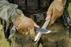 Il soldato con un coltello ha tagliato un bastone di legno fotografie stock