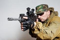 Il soldato con un fucile di assalto automatico immagine stock