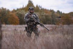 Il soldato con un fucile di tiratore franco sta nell'erba spessa immagine stock libera da diritti