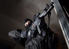 Il soldato delle forze speciali è tendente e sparante sull'obiettivo Immagine Stock