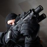 Il soldato delle forze speciali è tendente e sparante sull'obiettivo Immagini Stock