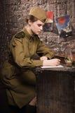 Il soldato femminile sovietico in uniforme della seconda guerra mondiale scrive una lettera Fotografie Stock