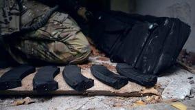 Il soldato prende il fucile dalla borsa stock footage