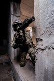 Il soldato russo dell'esercito spara una mitragliatrice dal nascondersi in una costruzione abbandonata immagine stock