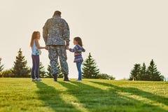 Il soldato sta parlando con le figlie, vista posteriore fotografia stock libera da diritti