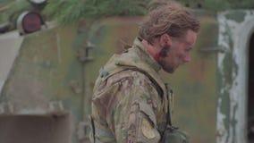 Il soldato ucraino ferito nello sbattimento va vicino ad un carro armato stock footage