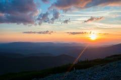Il sole arancio discende sull'orizzonte sopra le catene montuose Immagine Stock