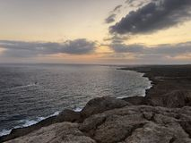Il sole aumenta ed è visto da dietro le montagne, sull'orizzonte la linea costiera del mare, è progettato una chiara estate afosa fotografia stock libera da diritti