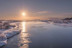 Il sole basso ha riflesso fuori dalle acque ghiacciate del lago Thingvallavatn immagine stock