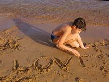 Il sole bello del Preteen ha abbronzato il ragazzo sull'amore del whrite della spiaggia del Mar Rosso Immagini Stock