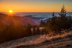 Il sole di mattina penetra la nebbia e illumina le montagne e le nuvole Immagine Stock