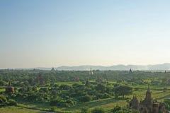 Il sole di sera splende nebbioso sopra le pianure del tempio di Bagan in Birmania fotografia stock
