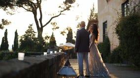 Il sole di sera splende sopra le coppie splendide che camminano fuori stock footage