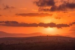 Il sole emette luce dietro le nuvole porpora in un cielo intenso di rosso arancio immagine stock libera da diritti