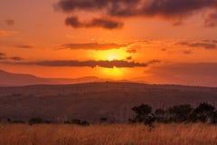 Il sole emette luce dietro le nuvole in un tramonto intenso sopra l'Africa immagini stock libere da diritti