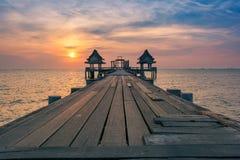 Il sole ha riflesso fuori dal ponte di legno che allunga nel Fotografia Stock