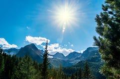 Il sole luminoso sopra la montagna completa su cielo blu con le nuvole bianche Immagini Stock