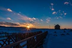 Il sole mette dietro le montagne e colora le nuvole nell'inverno, Altai, Russia fotografia stock libera da diritti
