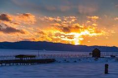 Il sole mette dietro le montagne e colora le nuvole nell'inverno, Altai, Russia immagini stock