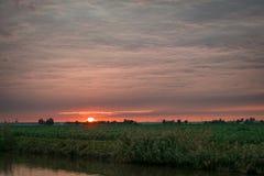 Il sole mette sopra la campagna olandese e splende sulla parte di sotto di uno strato della nuvola fotografia stock libera da diritti