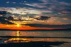 Il sole si siede in nuvole sopra il lago, gabbiani sorvola il wat Immagine Stock