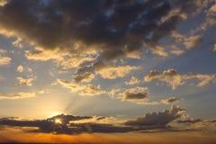 Il sole sta andando giù ed il cielo con il lotto delle nuvole Immagini Stock
