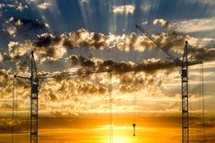 Il sollevamento cranes lavorare al bello cielo nuvoloso con il tramonto dorato Immagini Stock