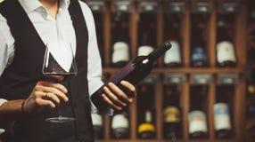 Il sommelier assaggia il vino rosso e legge l'etichetta della bottiglia, primo piano sparato sul fondo della cantina immagini stock