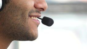 Il ` sorridente s dell'uomo affronta la conversazione facendo uso del micro della cuffia avricolare stock footage