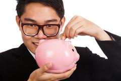 Il sorriso asiatico dell'uomo d'affari ha messo una moneta ad un porcellino salvadanaio rosa Fotografie Stock Libere da Diritti