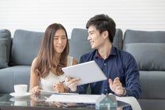 Il sorriso asiatico delle coppie sta progettando felicemente di sviluppare la sua casa in fotografia stock libera da diritti