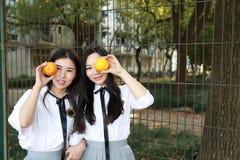 Il sorriso cinese della studentessa della High School dell'Asia di bellezza adorabile di Bestie gode del tempo libero sull'aranci Fotografia Stock Libera da Diritti