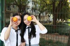 Il sorriso cinese della studentessa della High School dell'Asia di bellezza adorabile di Bestie gode del tempo libero sull'aranci Immagine Stock Libera da Diritti